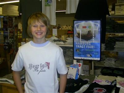 Nils mit seinem Gewinn, dem T-Shirt von Hamburg mal fair mit dem Motiv wear fair be fair im Süd-Nord-Kontor.